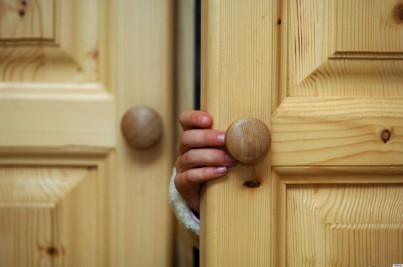 Hand of a child opening a cupboard door