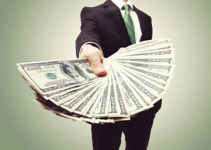 Business Man Displaying a Spread of Cash over a green vintage background